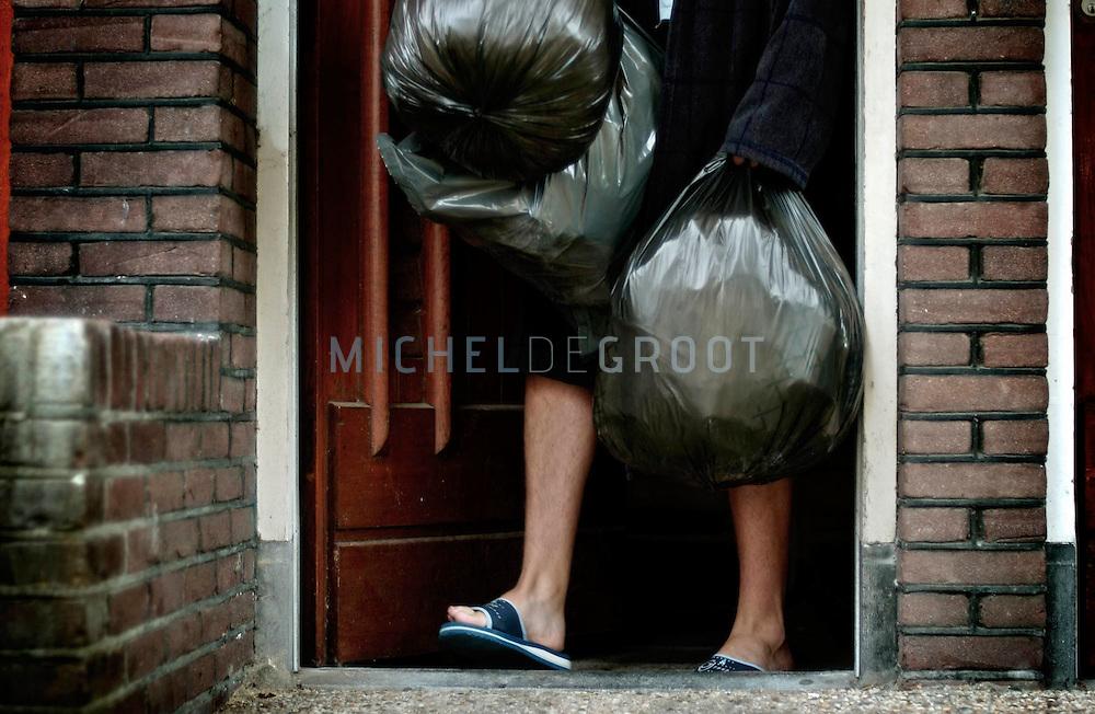 GRONINGEN, NETHERLANDS - 13-9-2003: HIERARCHIE IN STUDENTENHUIZEN. student zet het vuilnis buiten.