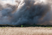A police officer guards the perimiter around a large tyre fire in Hounslow, west London in August, 2012.