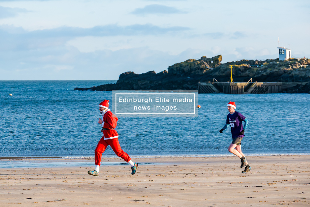 North Berwick, East Lothian, Scotland, United Kingdom, 28 November 2019. The annual Santa Run sees people and families running along West beach and the coastline to raise money to fund a Project Trust trip for school leaver Beth Poole, 18 years of age, to go to Ghana to teach English and maths at a junior school in the Volta region.<br /> Sally Anderson   EdinburghElitemedia.co.uk
