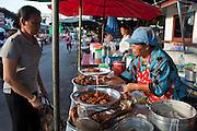 Sept. 23, 2009 -- BANGKOK, THAILAND: A street vendor prepares fried food for a client in the Khlong Toey slum area of Bangkok. Khlong Toey slum in Bangkok, Thailand, is the largest slum area in Bangkok. Photo by Jack Kurtz