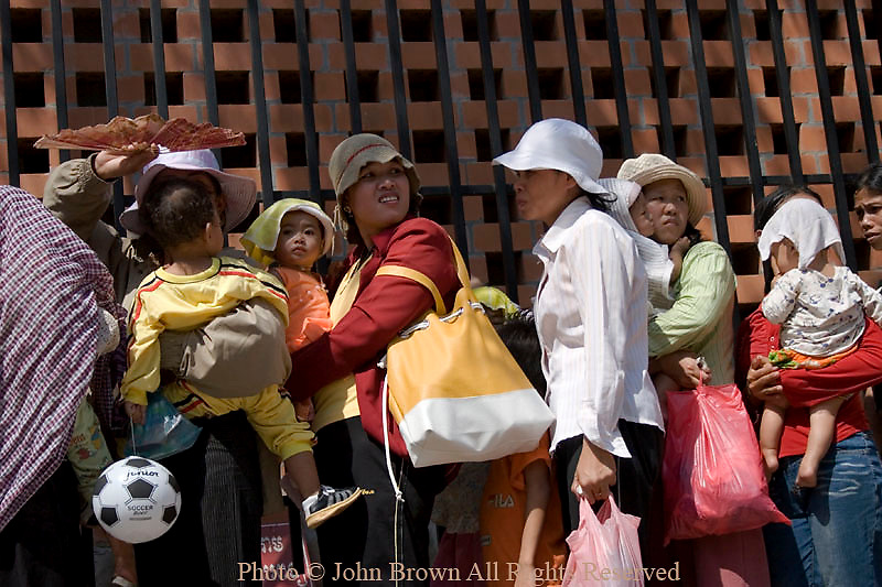 Women are waiting in a long line with their young children as they await free medical treatment at the world famous Bopha Hospital & Clinic in Phnom Penh, Cambodia. The Bopha Clinic treats thousands of children annually and is the largest such hospital in Cambodia.
