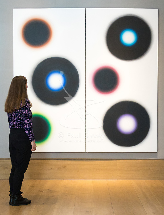 Bonhams, London, March 6th 2017. Fine art auctioneers Bonhams hold a preview in London  for their upcoming Post-War and Contemporary Art Sale which takes place on March 8th 2017. PICTURED: A woman admires  Wojciech Fangor's diptych 'NJ15' from 1964 which is expected to fetch between £140,000 and £180,000..