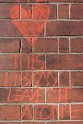 Protest writing on an Edwardian red brick pillar outside Carnegie Library in Herne Hill, south London while occupiers remain inside the premises on day 6 of its occupation, 5th April 2016. The angry local community in the south London borough have occupied their important resource for learning and social hub for the weekend. After a long campaign by locals, Lambeth have gone ahead and closed the library's doors for the last time because they say, cuts to their budget mean millions must be saved.