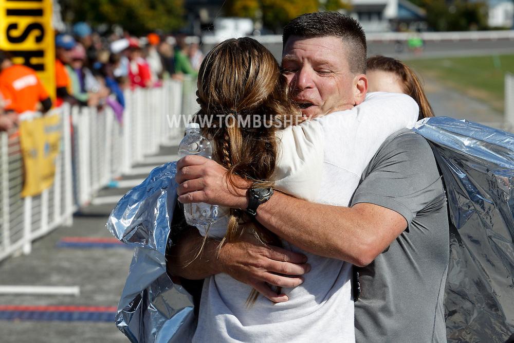 Goshen, New York  - A runner get a hug after finishing the Hambletonian Marathon on Sunday, Oct. 20, 2013.