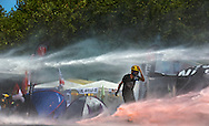 A protester walks amid water cannon spray while activist tents are seen near Gezi Park in Taksim Square, Istanbul, Turkey, 11 June 2013. Police used water cannons and tear gas as they moved into Istanbul's Taksim Square, where two weeks of protests have been held, as some demonstrators threw rocks and Molotov cocktails. Authorities used construction machinery to clear barricades erected by the protesters around the central square as police entered it for the first time since 01 June after a crackdown on the demonstrations drew international condemnation.
