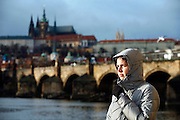 "SHOT 11/21/08 7:43:17 AM -  Portrait of Margaret Ebeling in front of the Charles Bridge and Prague Castle in Prague, Czech Republic. Prague is the capital and largest city of the Czech Republic. Its official name is Hlavní m?sto Praha, meaning Prague, the Capital City. Situated on the River Vltava in central Bohemia, Prague has been the political, cultural, and economic centre of the Czech state for over 1100 years. The city proper is home to more than 1.2 million people, while its metropolitan area is estimated to have a population of over 1.9 million. Since 1992, the extensive historic centre of Prague has been included in the UNESCO list of World Heritage Sites. According to Guinness World Records, Prague Castle is the largest ancient castle in the world. Nicknames for Prague have included ""the mother of cities"", ""city of a hundred spires"" and ""the golden city"". Since the fall of the Iron Curtain, Prague has become one of Europe's (and the world's) most popular tourist destinations. It is the sixth most-visited European city after London, Paris, Rome, Madrid and Berlin. Prague suffered considerably less damage during World War II than some other major cities in the region, allowing most of its historic architecture to stay true to form. It contains one of the world's most pristine and varied collections of architecture, from Art Nouveau to Baroque, Renaissance, Cubist, Gothic, Neo-Classical and ultra-modern..(Photo by Marc Piscotty / © 2008)"
