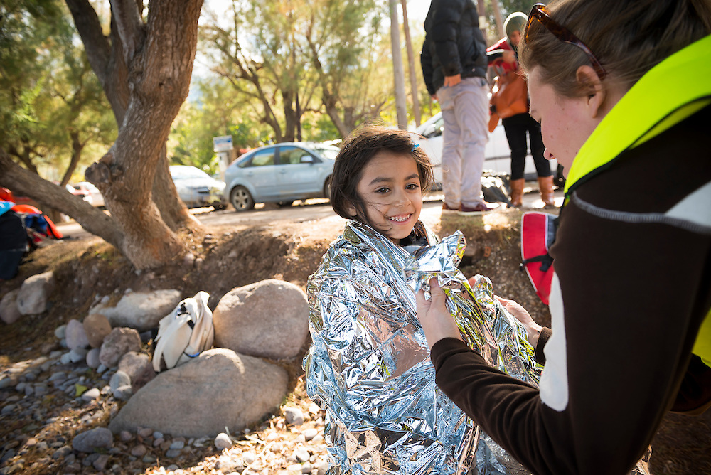 A volunteer from Norway assists a young girl who, with her family and other migrants, just landed on the Greek island of Lesbos, near the town of Skala Sikamineas. The volunteer helped remove the girl's life jacket and then wrapped her in a foil blanket for warmth.