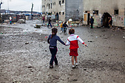 Two girl walking hand in hand in front of a decrepit building at the Roma settlement in Moldava nad Bodvou (2015). From about 800 inhabitants of the segregated settlement 'Budulovska Street' are roughly 392 children up to the age of 16 years (2014) .