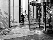As one man pushes his way out through the revolving doors of his office building another heads in with his bagged lunch in his hand. Seen at an office tower nar Battery Park, New York City.
