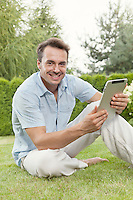 Portrait of smiling young man using tablet computer in park