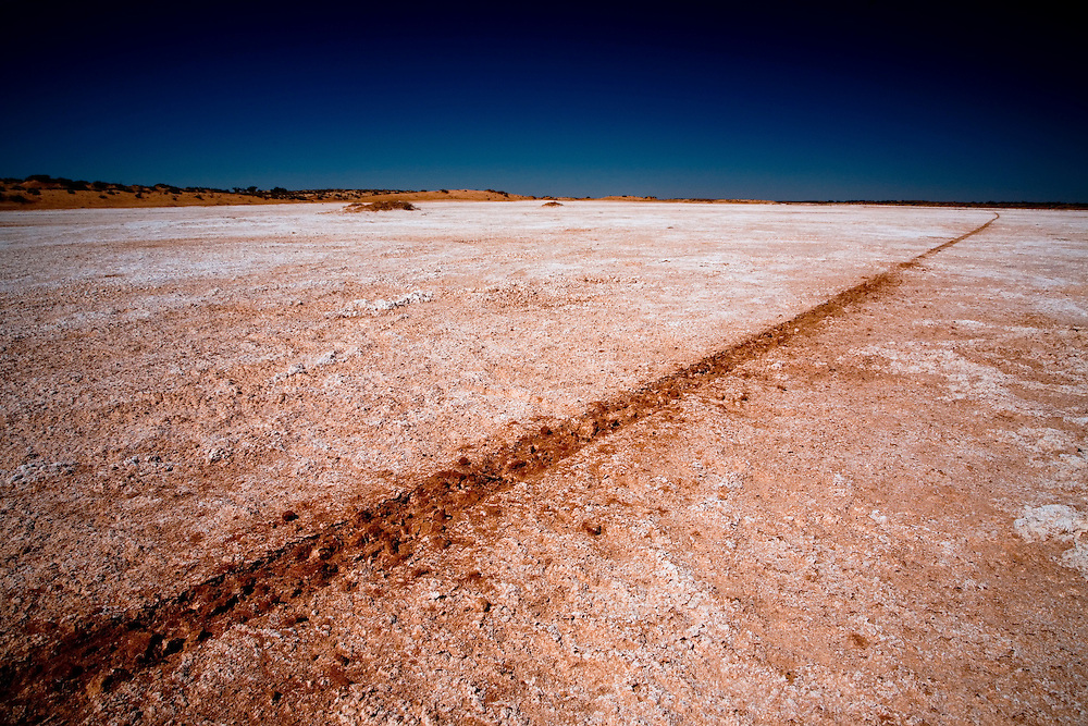 A single tire track travels into the distance across the remains of a salt lake in the Simpson Desert.