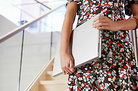 Businesswoman holding Laptop on Staircase mid section