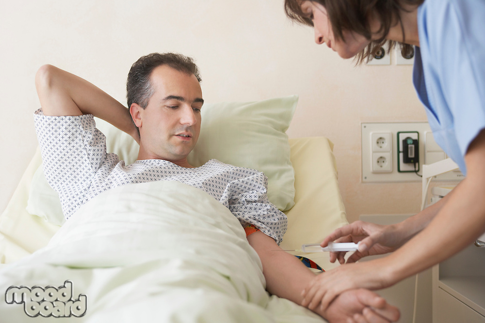 Nurse Giving Patient Injection in hospital bed