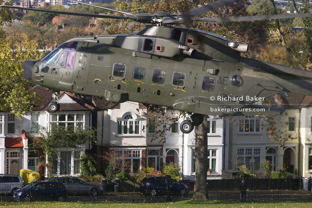 An AgustaWestland AW101 makes a controlled landing in a south London public park. After circling for 5 minutes in windy conditions and hovered metres above the ground n Ruskin Park, south London. Autumn leaves flew in all directions in this regular landing point for the Royal Air Force and army. The RAF frequently make reconnaissance flights to this Lambeth open space for crew training purposes. The Merlin is a medium-lift helicopter used in both military and civil applications. It was developed by joint venture between Westland Helicopters in the UK and Agusta in Italy and was named the EH101 until 2007.  .