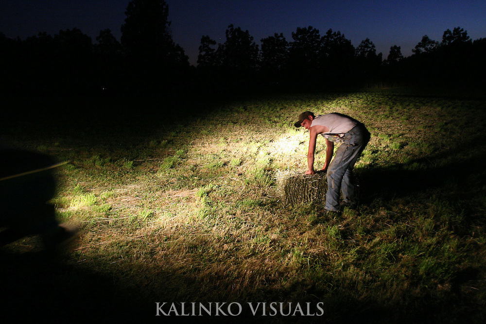 "Nick Vukich, 16, prepares to lift a hay bale as the lights from a pick-up truck illuminate the field at night Thursday July 12, 2007 in Enumclaw, Wash.  ""I do this because it's in my blood,"" Vukich said. ""My family has farmed on this land for many years and I want to carry that on."" Carrying on that traditional means spending long hours on the farm for many of the Green Valley's remaining farmers. Most farmers in the valley have day jobs in other types of work and only after a long day at the office do they find time to do their daily farm chores as well."