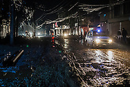A taxi drives down a main road during a rain storm, at night. Many of the roads in Kathmandu are littered with potholes and non-metalic.