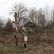 Natalia, school's teacher stands by the entrance of Maksimovichy village, where many houses were abandoned after Chernobyl's disaster. What was previously a prosperous area has become one of the poorest regions in Ukraine today