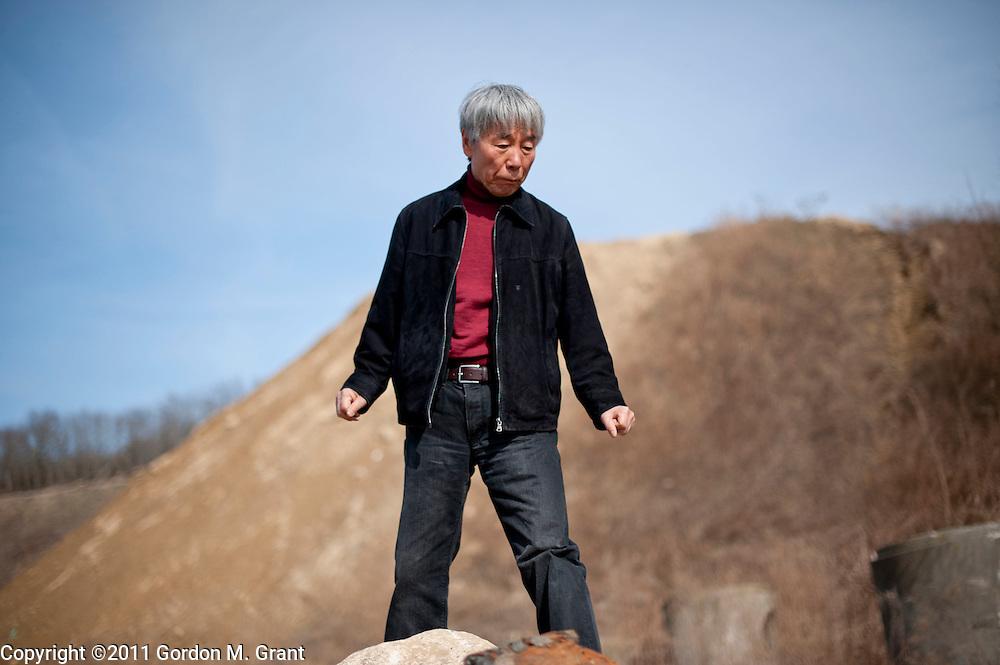 Bridgehampton, NY - 3/30/11 -   Lee Ufan, a Korean-Japanese artist, looks for rocks for his minimalist sculptures in a quarry in Bridgehampton, NY March 30, 2011.     (Photo by Gordon M. Grant)