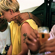 An Indian refugee drinks beer and carasses a Polish prostitute at a asylum home in Guben, in eastern Germany on the Polish border. .Picture taken 2000 by Justin Jin. ..