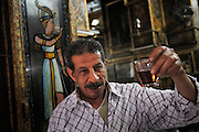 The owner of El Shems, a traditional tea and coffee house (ahwa) with his incredible kitsch furnishing. Cairo's ahwa (the traditional coffeehouse) are for Cairo what the pub is to London or caffè to Rome. Once the ahwa was the main place for entairnement, a animated place where Cairo's men socialised playing chess, backgammon or domino, reading newspapers or watching TV, drinking Turkish coffee and shai (tea) with mint or smoking a sheesha, the tradional waterpipe. Some ahwa are meeting places for people loving chess or remembering famous Egyptian singer Oum Kalthoum. Today Cairo is changed and everybody is just too busy to drink coffee in a ahwa, so western style coffee shops are much more than traditional ahwa.