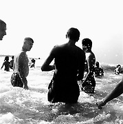 Teenagers and children playing in the sea, Three men in foreground, 1980's