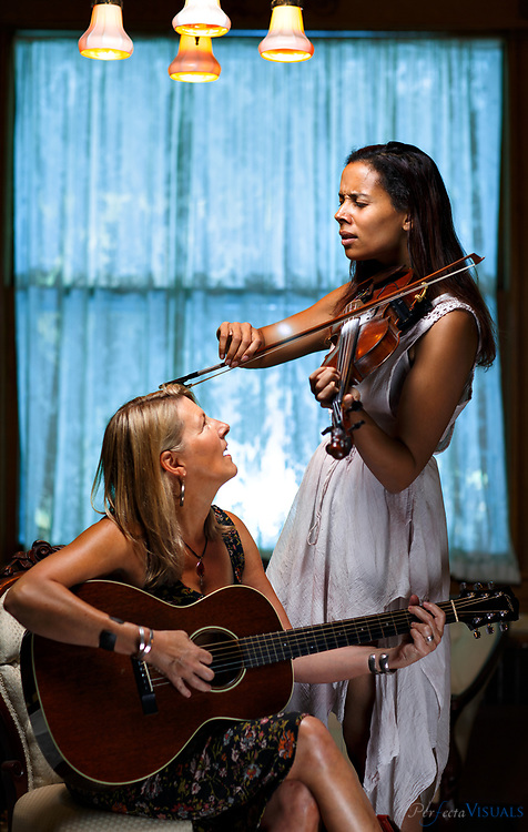 Singer/songwriter Laurelyn Dosset plays her guitar with fellow musician Rhiannon Giddens, as she plays her fiddle in the historic Warfield House Bed & Breakfast in Elkins, West Virginia, Wednesday, August 5, 2015.The two are teaching at a music workshop at  the Augusta Heritage Center of Davis & Elkins College in Elkins, West Virginia.