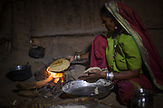 Sheela makes chapatis on an open fire in her kitchen, Sendhwa, India.