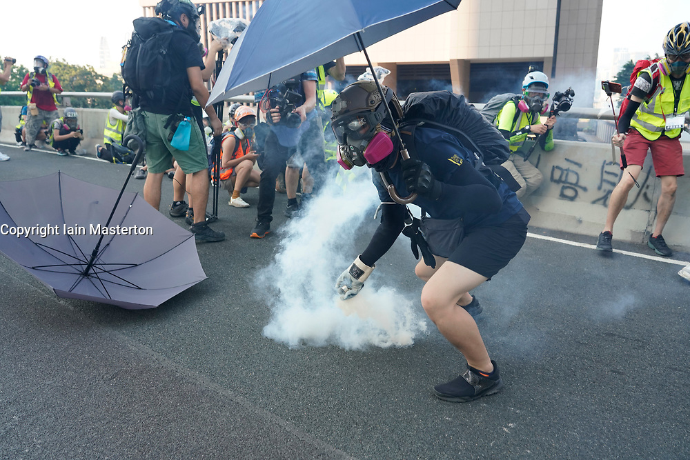 Hong Kong. 1 October 2019. After a peaceful march through Hong Kong Island by an estimated 100,000 pro democracy supporters, violent flared up at Tamar, Admiralty and moved through Wanchai district. Police used teargas and baton rounds and water cannon. Hard core group lit fires, threw bricks and Molotov cocktails at police. Violence continues into evening. Protestor returns police teargas canister. Iain Masterton/Alamy Live News.