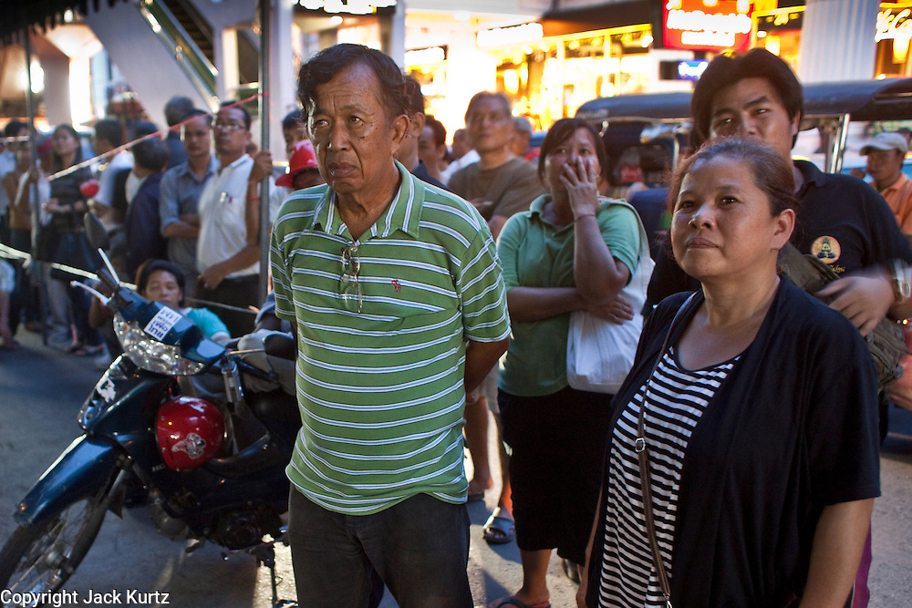 "06 MAY 2010 - BANGKOK, THAILAND: Red Shirts watch television as it's announced that negotiations between the Reds and the government have broken down. Many of the Red Shirts are farmers who need to return to their land to start planting their crops. Red Shirt protestors in Ratchaprasong intersection, Thursday May 6, more than one month after the Reds occupied the intersection. Members of the United Front of Democracy Against Dictatorship (UDD), also known as the ""Red Shirts"" and their supporters moved their anti government protests into central Bangkok Apr. 4 when they occupied Ratchaprasong intersection, the site of Bangkok's fanciest shopping malls and several 5 star hotels. The Red Shirts are demanding the resignation of current Thai Prime Minister Abhisit Vejjajiva and his government. The protest is a continuation of protests the Red Shirts have been holding across Thailand. They support former Prime Minister Thaksin Shinawatra, who was deposed in a coup in 2006 and went into exile rather than go to prison after being convicted on corruption charges. Thaksin is still enormously popular in rural Thailand. This move, away from their traditional protest site in the old part of Bangkok, has gridlocked the center of the city and closed hundreds of stores and restaurants and several religious shrines. On Thursday night the Red Shirt leaders said there has been a ""glitch"" in the ongoing negotiations to end the standoff. Their opponents, the ""Yellow Shirts"" who previously supported the incumbent Prime Minister have rejected his peace plan and called for the PM to resign.  PHOTO BY JACK KURTZ"