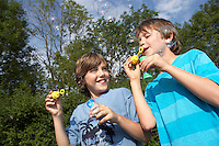 Two young boys blowing soap bubbles in park