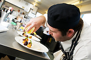 Chef drizzling sauce onto gourmet appetizers during a catering and cooking competition