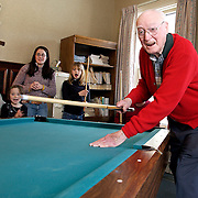 Fayetteville, NY / 2005 - Bob Brown (right) reacts after shooting the eight ball into a pocket during a friendly game of pool at the Fayetteville Senior center. Watching the game in the background are (from left) Ashley Twichell, age 15, Molly Quinlan, age 6, Laura Twichell, age 16, and Haley Quinlan, age 11.  The pool table was donated to the center by a local community member who moved to Florida and wanted the table to be used for a good cause. Photo by Mike Roy / For The Syracuse Post-Standard