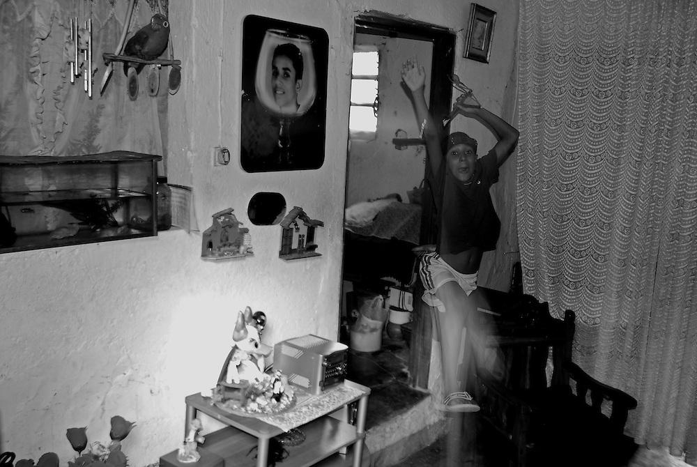 APUNTES SOBRE MI VIDA: LA PASTORA I - 2009/10<br /> Photography by Aaron Sosa<br /> Marco Antonio Montilla, saliendo de la antigua habitación de Maikel Montilla. En la foto colgada en la pared se puede apreciar a Edgar Montilla (otro gran amigo), hermano de Maikel, fue asesinado a la edad de 18 años hace más de 10 años.<br /> La Pastora, Caracas - Venezuela 2009<br /> (Copyright © Aaron Sosa)