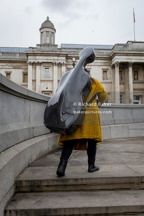 A lady carries a cello case up the steps in front of the National Gallery in Trafalgar Square, on 29th March, 2018 in London, England.