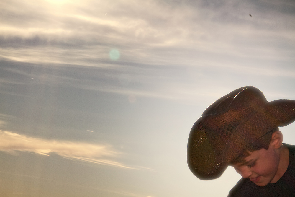 A young cowboy looks downward against a shimmering sunlight.