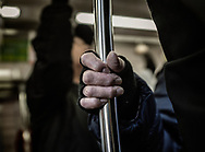 Grasping pole on the train through fingerless gloves.  Tokyo, Japan