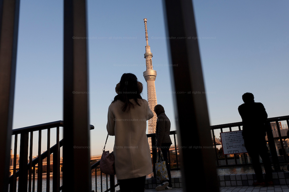Tourists look at Tokyo Skytree from a small riverside park in Asakusa, Tokyo, Japan Sunday February 10th 2013