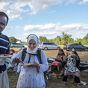 "DUMFRIES, VA - SEP12: Hanane and Mohamed Elsanousi, enjoy some freshly grilled goat meat at the Shah Farm in Dumfries, VA, September 12, 2016, during the Muslim holiday, Eid al-Adha, the ""Feast of the Sacrifice"". (Photo by Evelyn Hockstein/For The Washington Post)"