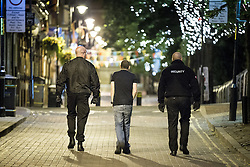 """© Licensed to London News Pictures . 10/08/2011 . Manchester , UK . Jeremy Joseph (c) walks along Canal Street in Manchester's """" Gay Village """" , flanked by security guards , as disorder spreads to Manchester during a 4th night of rioting and looting , following a protest against the police shooting of Mark Duggan in Tottenham . Photo credit : Joel Goodman/LNP"""