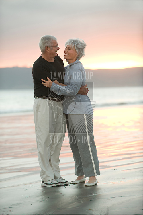 Senior couple hugging on the beach at dusk