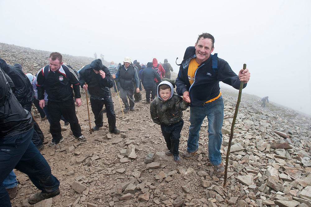 seven year old Andrew and his dad Patrick from Keadue, Co. Roscommon make their way up the mountain, this is Andrews first time on pilgrimage to  Croagh Patrick, Co. Mayo. Pic: Michael Mc Laughlin Thousands of pilgrims navigate up and down the rugged slopes of croagh Patrick in honour of our Patron Saint, Saint Patrick, Ireland's Holy Mountain, Co. Mayo. Pic: Michael Mc Laughlin