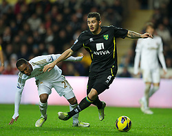 SWANSEA, WALES - Saturday, December 8, 2012: Swansea City's Jonathan De Guzman in action against Norwich City's Bradley Johnson during the Premiership match at the Liberty Stadium. (Pic by David Rawcliffe/Propaganda)