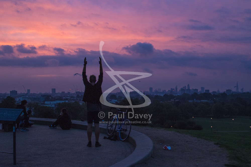 Primrose Hill, London, September 22nd 2016. A cyclist stretches on Primrose Hill as the autumn equinox sun rises over London . ©Paul Davey<br /> FOR LICENCING CONTACT: Paul Davey +44 (0) 7966 016 296 paul@pauldaveycreative.co.uk