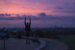 Primrose Hill, London, September 22nd 2016. A cyclist stretches on Primrose Hill as the autumn equinox sun rises over London . &copy;Paul Davey<br /> FOR LICENCING CONTACT: Paul Davey +44 (0) 7966 016 296 paul@pauldaveycreative.co.uk