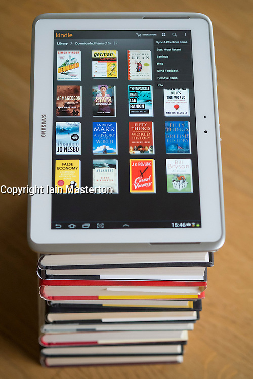 Samsung Galaxy Note 10 tablet computer with kindle e-book library application and pile of traditional hardback paper books
