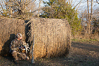 DEER HUNTER WITH A MOSSBERG SHOTGUN AND WEARING REALTREE CAMOUFLAGE HIDING BEHIND HAY BALES USING ANTLERS TO RATTLE DEER