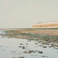 Sandy puddles on Old Hunstanton Beach, cliffs in the distance
