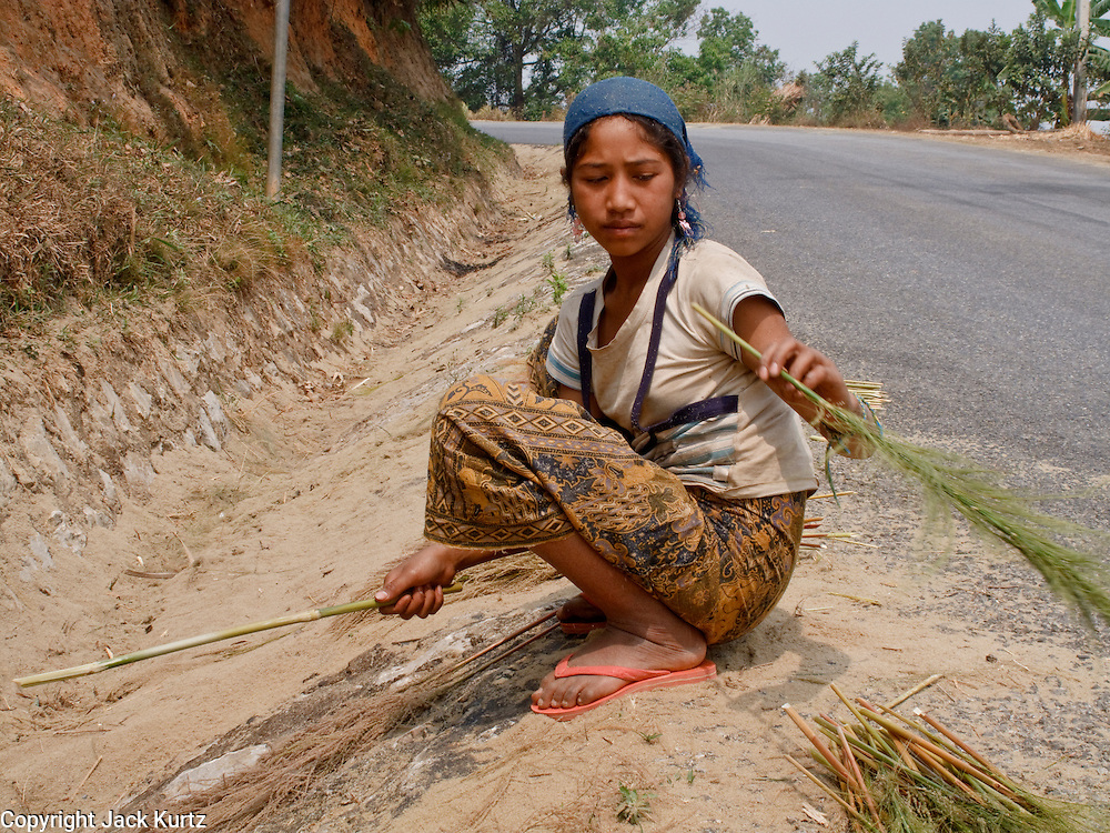 Mar. 16, 2009 -- LUANG PRABANG, LAOS: A woman makes brooms along the side of the road in a village on Highway 13 south of Luang Prabang, Laos. Highway 13 is the main highway in Laos and carries tourist and truck traffic between the capital Vientiane and Luang Prabang. Photo by Jack Kurtz