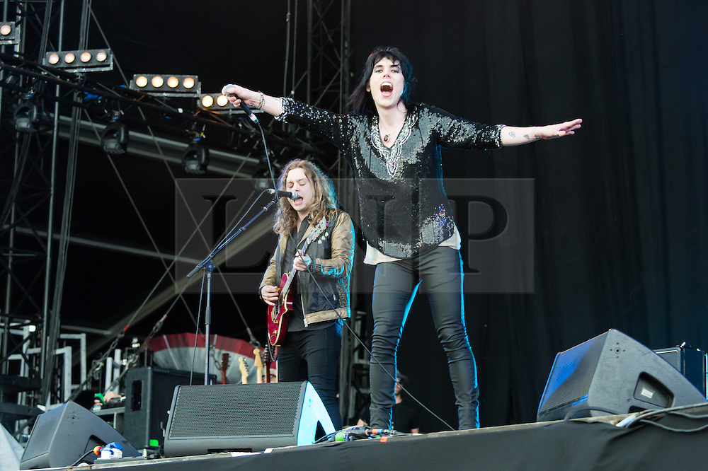 © Licensed to London News Pictures. 12/06/2015. Newport, UK.   The Struts performing live at Isle of Wight Festival 2015..  It started raining in the first two songs of the band being on stage, with rain having been forecast for the weekend after the last day of hot sunshine.  In this picture - Luke Spiller.Photo credit : Richard Isaac/LNP