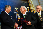 Speaker of the House JOHN BOEHNER awards golf legend ARNOLD PALMER the Congressional Gold Medal during a ceremony on Capitol Hill Wednesday. Congress awarded the medal to Palmer for his contributions to the game of golf and his civic contributions to the nation. Senate Majority Leader HARRY REID steals a peek at the medal.